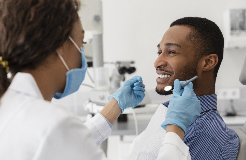 Dental patient smiling during teeth cleaning in Denver CO